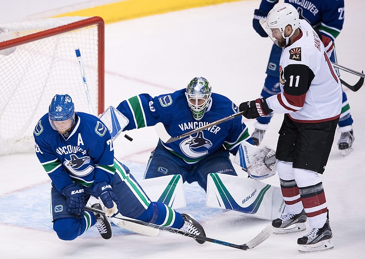 Vancouver Canucks' Alexander Edler, left, of Sweden, deflects the puck wide of the net in front of goalie Jacob Markstrom, of Sweden, as Arizona Coyotes' Martin Hanzal, right, of the Czech Republic, watches during the second period of a preseason NHL hockey game in Vancouver, British Columbia, Monday, Oct. 3.