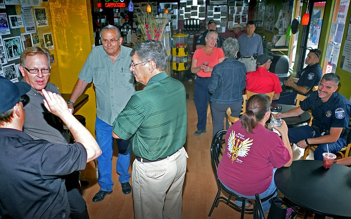Interim Police Chief Chris Vasquez, center, talks with Winslow community members at the first Coffee with a Cop at Mojo's Coffee House Sept. 27. The nation wide program allows community members and police officers to talk in a relaxed atmosphere. Todd RothNHO