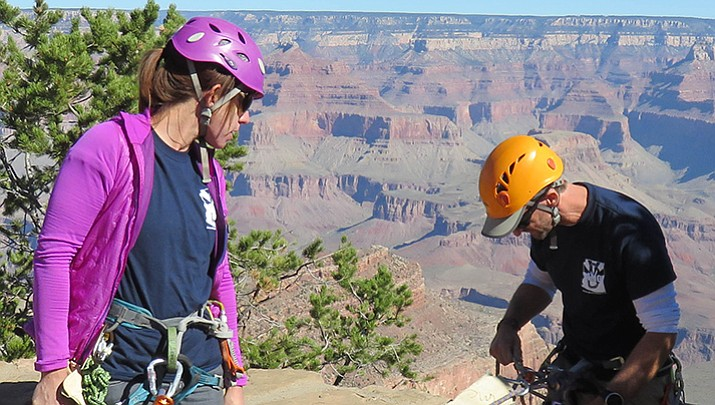 Laura and John Carr secure their rappelling equipment as John prepares to descend over the rim just beneath the El Tovar Hotel.