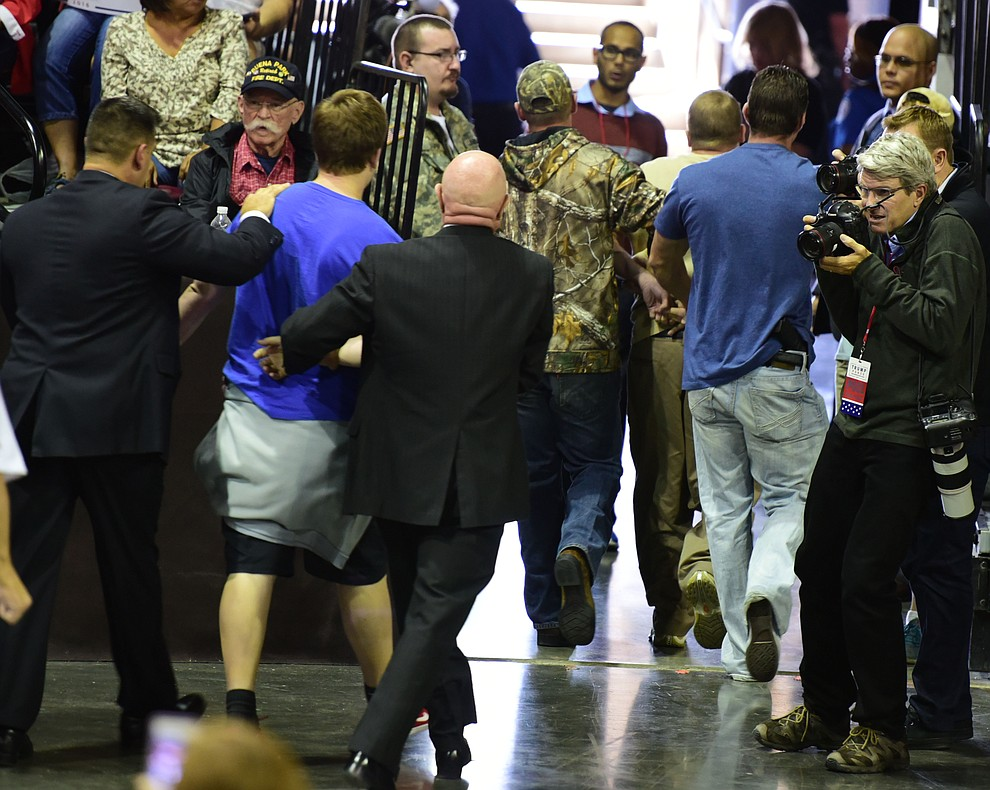 Three people who caused a disturbance are escorted from the arena at the Donald Trump for President Rally in the Prescott Valley Event Center Tuesday, October 4, 2016. (Les Stukenberg/The Daily Courier)