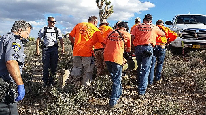 Sgt. Mike Ramirez, left, supervises the scene while Mohave County Search & Rescue coordinator Deputy Joey McEuen watches volunteers recover a fatal accident victim.