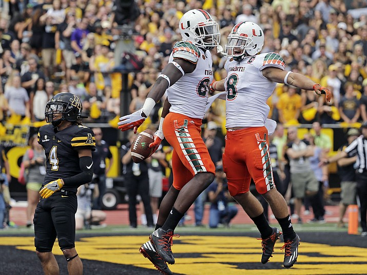 Miami's David Njoku celebrates with Braxton Berrios, right, after a touchdown catch Sept. 17 during an NCAA college football game in Boone, N.C. The Miami Hurricanes have lost six straight to the Florida State Seminoles and nine of 11 in series that had a run in the late 1980s and early 1990s of often producing the most important college football game of the season.
