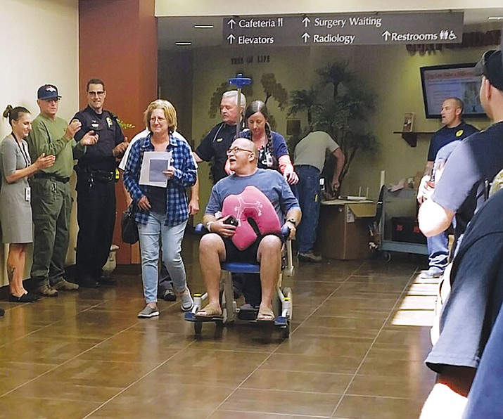 Detective Dennis Gilbert is cheered on in his wheelchair after being released from the hospital Wednesday. Gilbert was shot while serving a search warrant on Sept. 29.