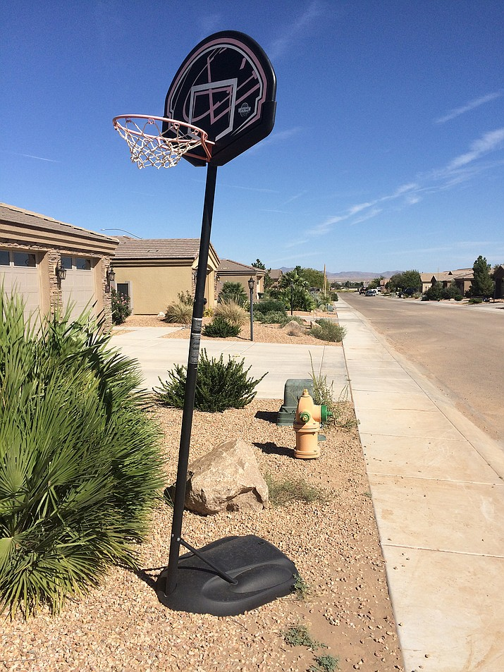 "A roll-away basketball hoop, left, sits just off the street in Walleck Ranch. Many Kingman subdivisions have rules against ""unsightly objects."""