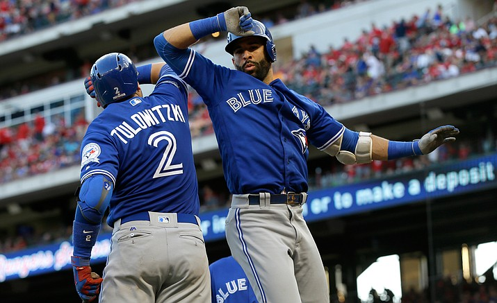 Toronto Blue Jays' Troy Tulowitzki (2) and Jose Bautista celebrate Bautista's three-run home run against the Texas Rangers during the ninth inning of Game 1 on Thursday afternoon in Arlington, Texas. The Blue Jays won 10-1.