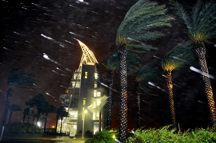 Trees sway from heavy rain and wind from Hurricane Matthew in front of Exploration Tower early Friday, Oct. 7, 2016 in Cape Canaveral, Fla. Matthew weakened slightly to a Category 3 storm with maximum sustained winds near 120 mph, but the U.S. National Hurricane Center says it's expected to remain a powerful hurricane as it moves closer to the coast.