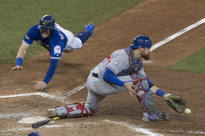 Toronto Blue Jays' Josh Donaldson, left, scores on a throwing error from Texas Rangers second baseman Rougned Odor as catcher Jonathan Lucroy gathers up the ball during the 10th inning of American League Division Series action, in Toronto on Sunday, Oct. 9.