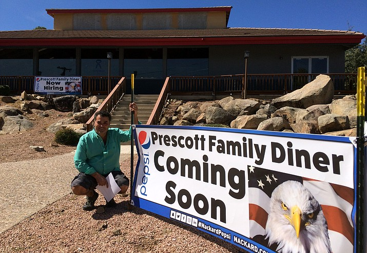 Tally Elbayomy kneels next to a sign he recently put up to promote the eventual opening of his new restaurant, Prescott Family Diner.