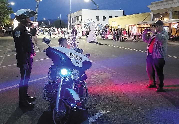 Kingman Police Officer Chaz Truver let passersby take pictures of their little ones sitting on a police motorcycle at Friday's Pink Heals block party downtown.