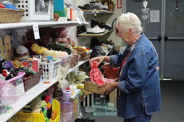 Volunteer Carole Fuller stocks the shelves Thursday at Grandma's Treasure Thrift Store on Airway Avenue in Kingman.