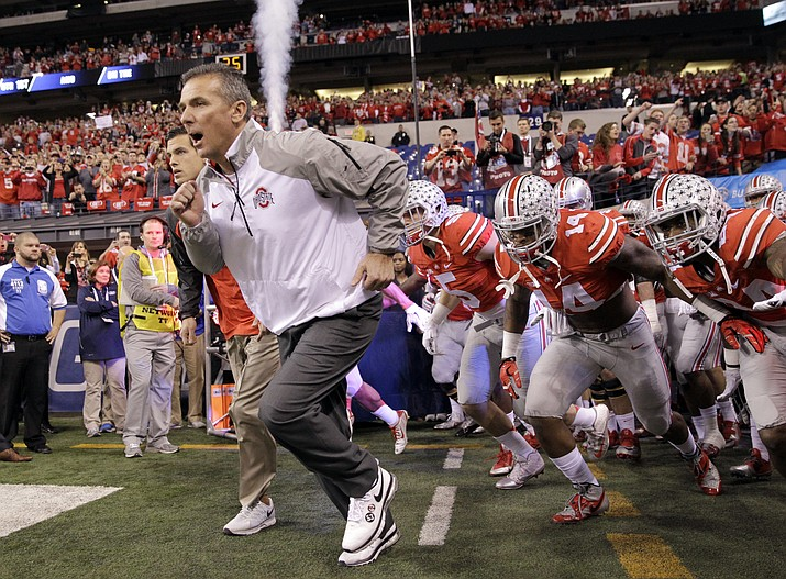 Ohio State head coach Urban Meyer runs onto the field with his team at the start of the 2014 Big Ten Conference championship NCAA college football game against Wisconsin in Indianapolis. If No. 1 Alabama and No. 2 Ohio State are going to lose this season, this would be an excellent week to do so. The Crimson Tide take on No. 9 Tennessee, while the Buckeyes take on No. 8 Wisconsin.