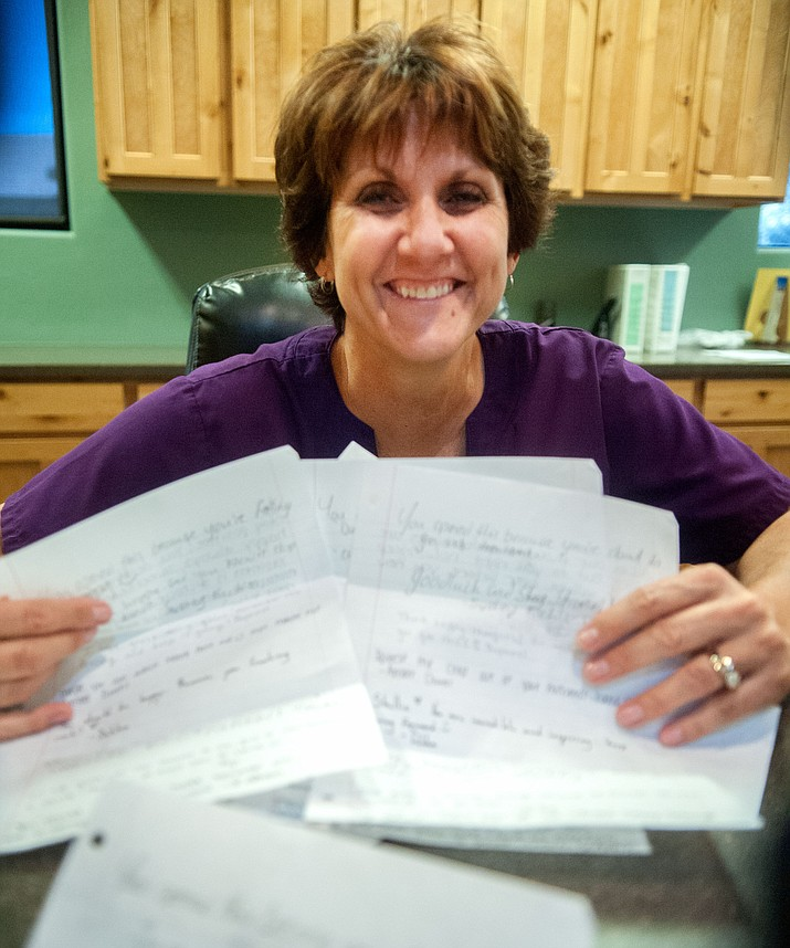 Former Prescott High School volleyball coach Shellie Bowman continues to smiles three years after being diagnosed with breast cancer as the disease is still in remission. Bowman is holding some of the letters and notes from her former players that were messages of hope for her.