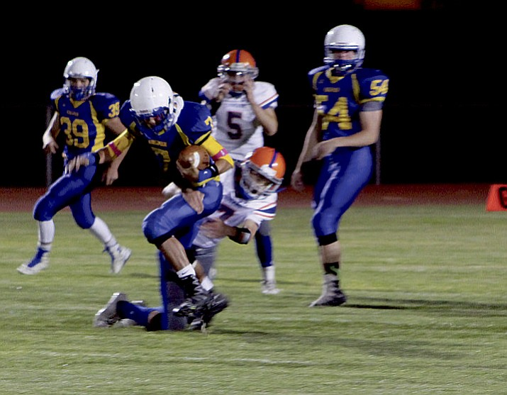 Kingman's Miguel Salinas (7) tries to get rid of a Chino Valley defender during the Bulldog's 35-14 loss Friday at KHS. Salinas rushed for 103 yards and accounted for 227 total yards. (Shawn Byrne/Kingman Daily Miner)