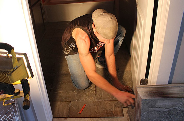 Jason Holloway places tile in the corner of a bathroom Wednesday at a new home on Horsemint Avenue, off Slaughterhouse Canyon Road.
