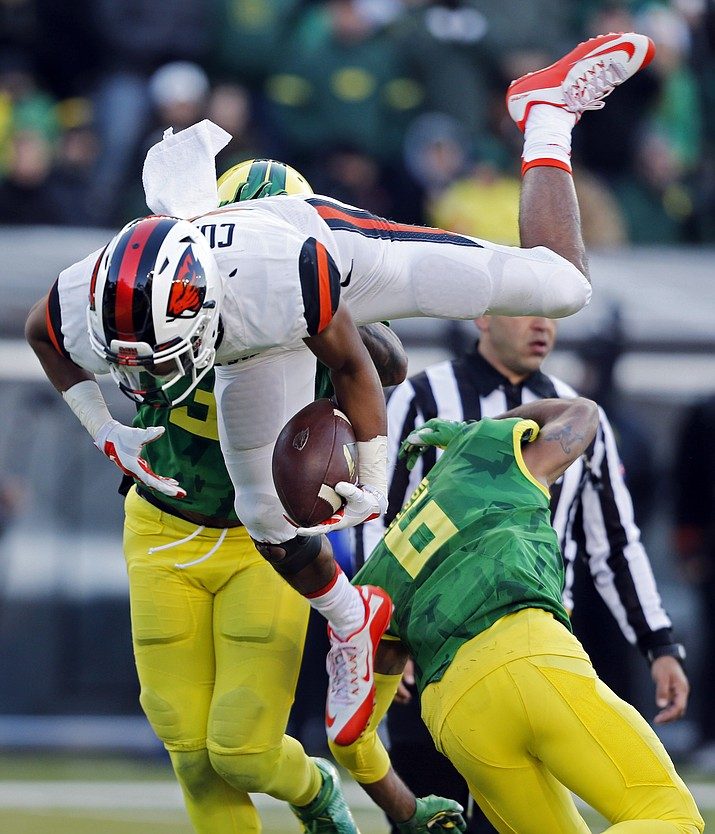 Oregon State's Seth Collins leaps over Oregon's Charles Nelson for a touchdown in the Nov. 27, 2015, NCAA college football game in Eugene Ore. The change in positions for Collins seemed inevitable at the end of last season, when he was used in several roles in the finale against Oregon.
