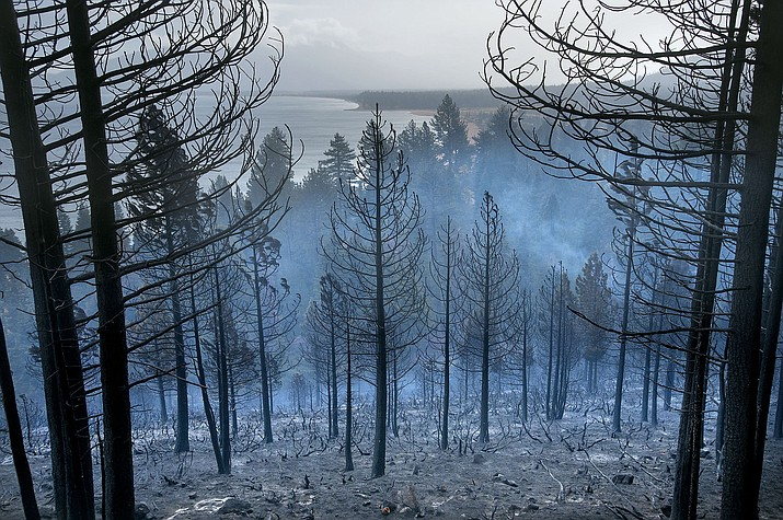 Lake Tahoe can be seen behind the Emerald Fire along Highway 89, Friday, Oct. 14, 2016 near Lake Tahoe, Nev. A wind-whipped wildfire raged out of control Friday in northern Nevada, destroying more than a dozen homes, forcing evacuations, closing roads and schools, and triggering power outages, officials said.