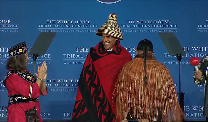 Tribal leaders dress President Barack Obama in traditional Native American garb before his remarks to the eighth annual conference of tribes organized by his administration.