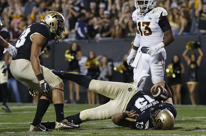 Colorado quarterback Sefo Liufau, front right, tumbles into the end zone for a touchdown as running back Phillip Lindsay, front left, looks on with Arizona State defensive back Armand Perry in the first half Saturday in Boulder, Colo.