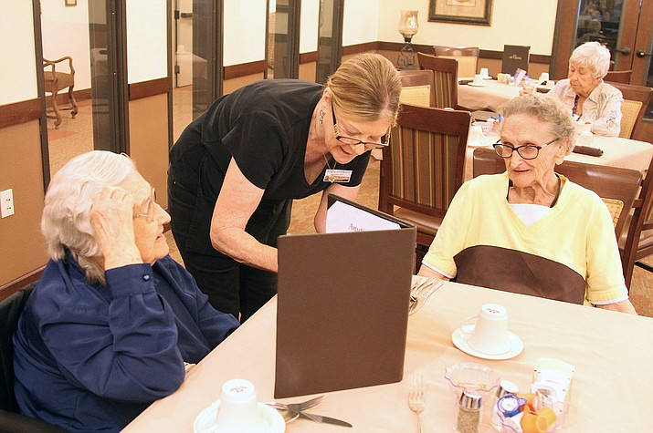 Kathy Kickwood (center) takes orders as Edith Wisniewski (left) and Hulda Watson get ready to eat something in the dining room at White Cliffs Senior Living last Thursday afternoon.