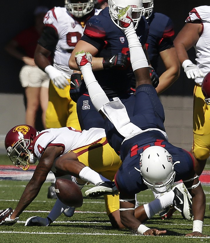 Southern California defensive back Chris Hawkins (4) upends Arizona quarterback Khalil Tate (14) during the first half Saturday in Tucson.