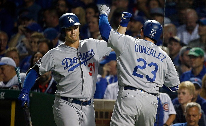 Los Angeles Dodgers' Adrian Gonzalez celebrates with Joc Pederson after hitting a home run during the second inning of Game 2 of the National League baseball championship series against the Chicago Cubs, Sunday, Oct. 16, in Chicago.