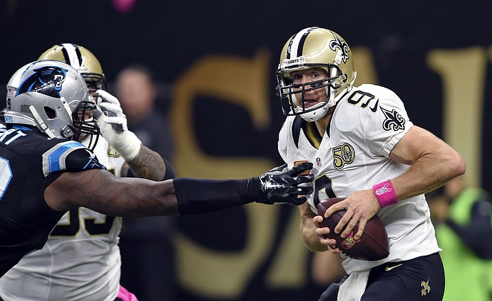 New Orleans Saints quarterback Drew Brees (9) scrambles under pressure from Carolina Panthers defensive tackle Kawann Short in the first half of an NFL football game in New Orleans, Sunday, Oct. 16.