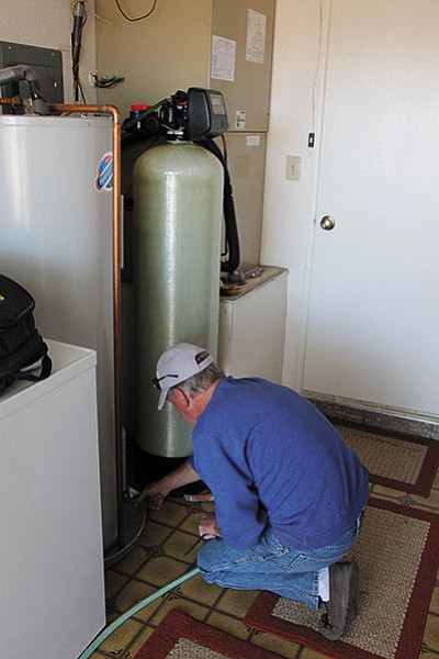 Valle Vista resident Jerry Hill disconnects a water hose next to his filtration system for arsenic. Truxton Canyon Water Co. installed a $350,000 treatment plant to reduce high levels of arsenic found in its water supply.
