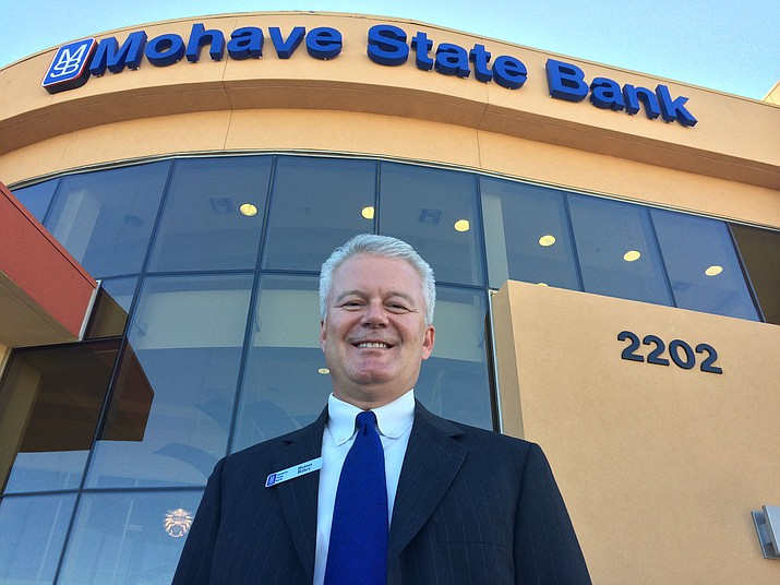 Mohave State Bank CEO Brian Riley stands in front of the bank's branch on Hualapai Mountain Road.