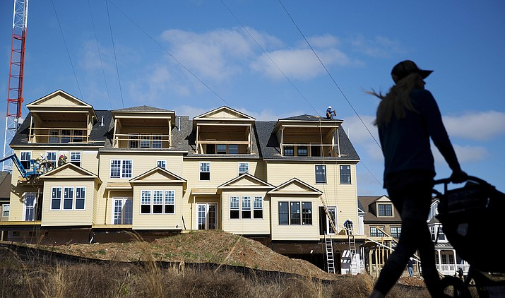 FILE - In this Wednesday, Feb. 17, 2016, file photo, town homes stand under construction as a pedestrian walks along the BeltLine in Atlanta. First-time buyers may be entering the U.S. home market in greater numbers than industry watchers had assumed. Nearly half of sales in the past year went to people who were buying their first home, according to a survey released Tuesday, Oct. 18, 2016, by the real estate firm Zillow. That's a much higher proportion of the market than other industry estimates had indicated. (AP Photo/David Goldman, File)