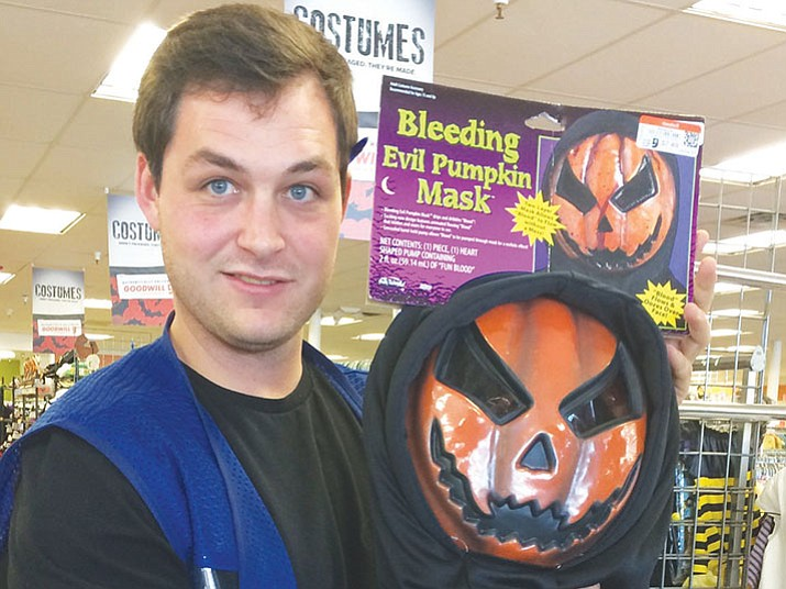 goodwill store associate trevor blish holds up a favorite pumpkin head mask - Halloween Stores In Az