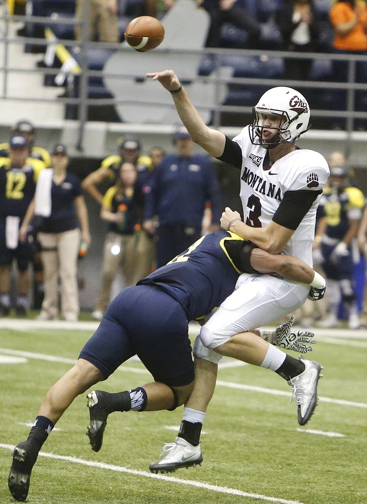 University of Montana quarterback Brady Gustafson (3) releases the ball as he is brought down by a Northern Arizona defender during an NCAA college football game at the Walkup Skydome in Flagstaff, Ariz. Saturday, Oct. 22, 2016.