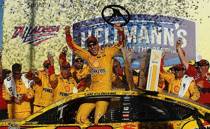 Joey Logano celebrates after winning the NASCAR Sprint Cup Series auto race auto race at Talladega Superspeedway, Sunday, Oct. 23.