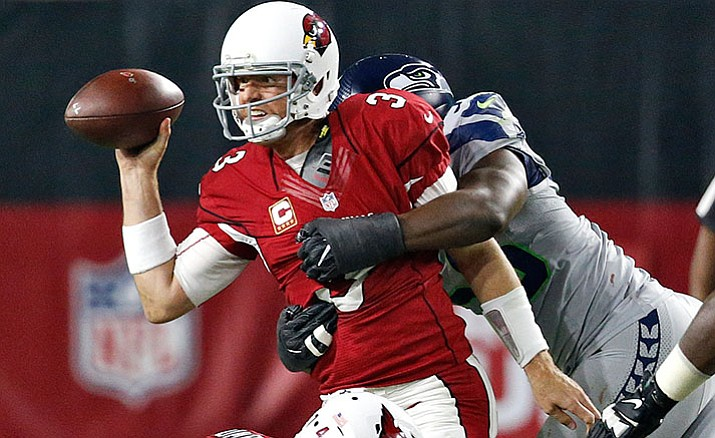 Arizona Cardinals quarterback Carson Palmer is hit by Seattle Seahawks defensive end Cliff Avril during the first half of a football game, Sunday, Oct. 23, in Glendale.