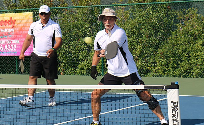 "Larry Cloud makes a play at the ""kitchen"" line during a pickleball tournament in August at the Prescott Lakes courts, while his partner Ben Sialega looks on."