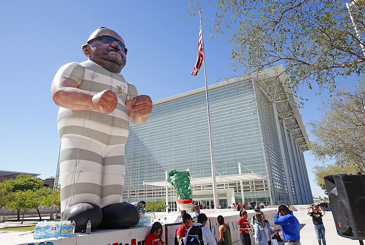 Protesters display an effigy of Maricopa Country Sheriff Joe Arpaio wearing prison clothes in front of U.S. District Court as prosecutors announce they will charge Maricopa County Sheriff Joe Arpaio with criminal contempt-of-court Tuesday, Oct. 11, 2016, in Phoenix. Arpaio is accused of defying a judge's orders to end his immigration patrols in Arizona, which if convicted could lead to jail time, as Arpaio seeks another term as Maricopa County Sheriff in less than a month.