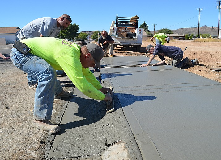 CL Woodward owner Charlie Woodward smooths poured concrete on a 25-foot portion of sidewalk south of the House of Gains.
