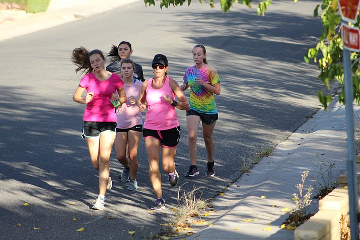 Lee Williams cross country coach Joan Abraham, with cap, runs with members of her girls team on Turquoise Street during Wednesday's practice in preparation for Friday's sectional race.