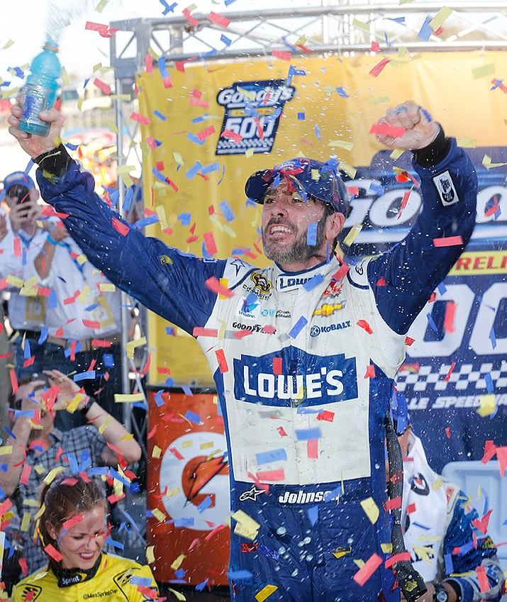 Jimmie Johnson celebrates after winning the NASCAR Sprint Cup Series auto race at Martinsville Speedway on Sunday, Oct. 30.