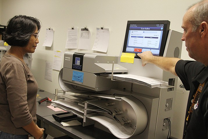 Nancy Krahulec, Mohave County Elections assistant, and Director Allen Tempert scan ballots with the DS850 high-speed digital ballot scanner on Friday.