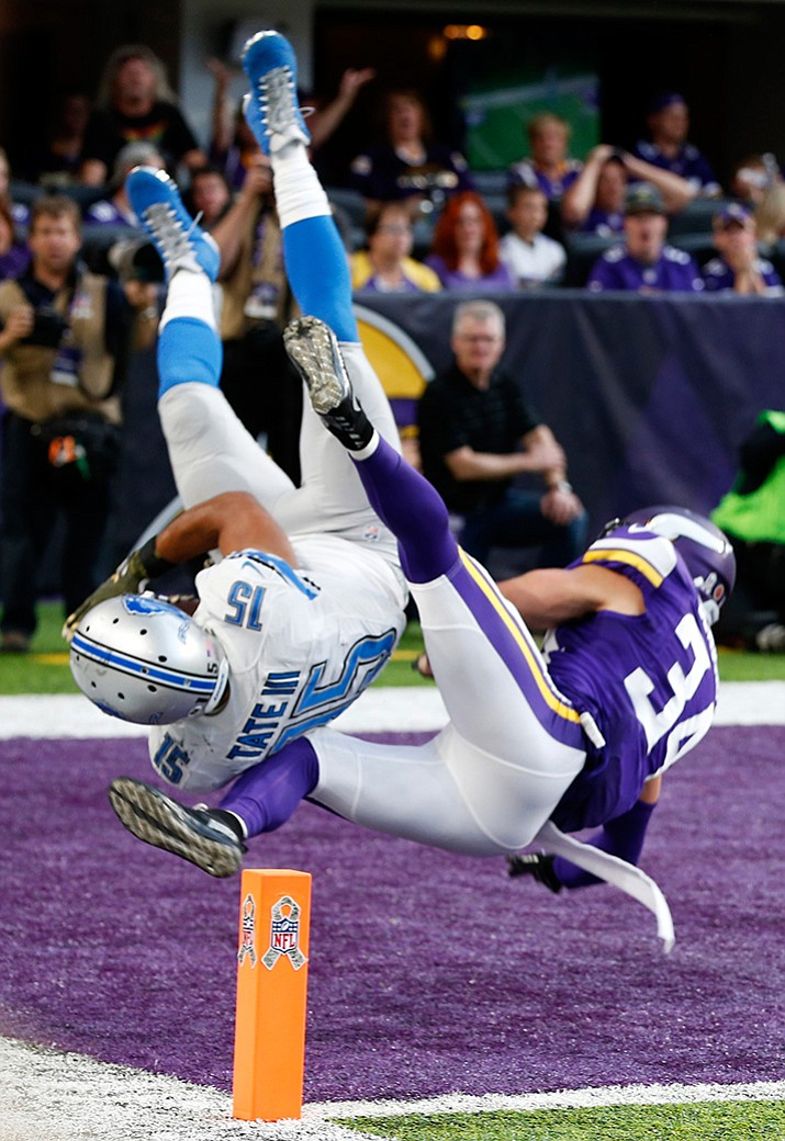 Detroit Lions wide receiver Golden Tate flips into the end zone in front of Minnesota Vikings strong safety Andrew Sendejo, right, after catching a 28-yard touchdown pass during overtime in an NFL football game Sunday, Nov. 6, in Minneapolis. The Lions won 22-16.