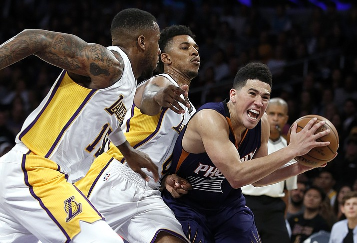 Los Angeles Lakers forward Thomas Robinson, left, and guard Nick Young, center, chase after Phoenix Suns guard Devin Booker, right, during the second half of an NBA basketball game in Los Angeles, Sunday, Nov. 6. The Lakers won 119-108.