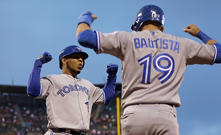 This May 9, 2016 file photo shows Toronto Blue Jays' Edwin Encarnacion, left, celebrating with Jose Bautista (19) after hitting a two run home run off San Francisco Giants' Jake Peavy in the third inning of a baseball game in San Francisco. Bautista and Encarnacion were among 10 players to receive $17.2 million qualifying offers from their teams Monday, Nov. 7, 2016 as general managers gathered for their annual meeting.