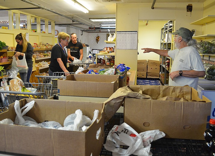 Kingman Area Food Bank volunteers load shopping carts with nutritionally proportioned amounts of food.