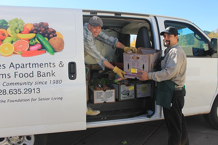 Safeway employee Frank Kramer helps Guy Mikkelsen load food donations from Safeway into the Williams Food Bank van.