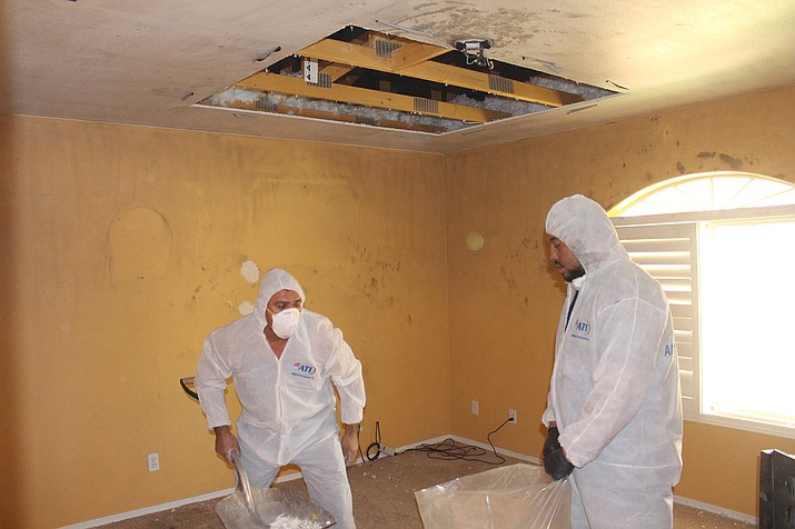 Samuel Gonzalez, and Adam Thomas clean up after a laptop exploded and caused a fire in a Golden valey home Nov. 5.