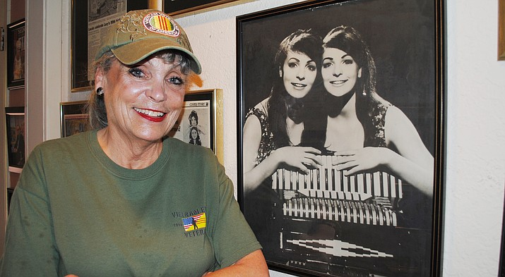 "Terrie Frankel, Verde Valley Military Park committee member, poses next to a picture of herself and twin sister, Jennie, during their Doublemint Twin days. Frankel, a former Vietnam USO performer, said the park is ""absolutely marvelous"" and looks forward to the Nov. 11 ribbon-cutting at Garrison Park in Cottonwood. (VVN/Jennifer Kucich)"