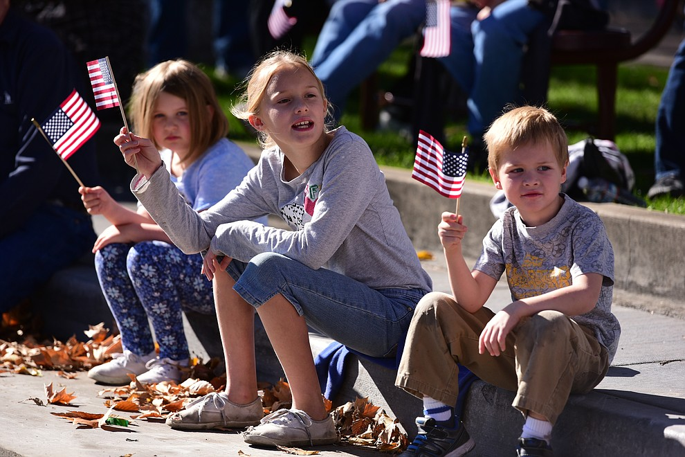 Isabella Golembieski, Hope Collins and Issac Collins wave their flags as crowds lined the streets as the 2016 Veterans Day Parade winds through the streets of downtown Prescott Friday morning. The parade featured over 90 entries.
