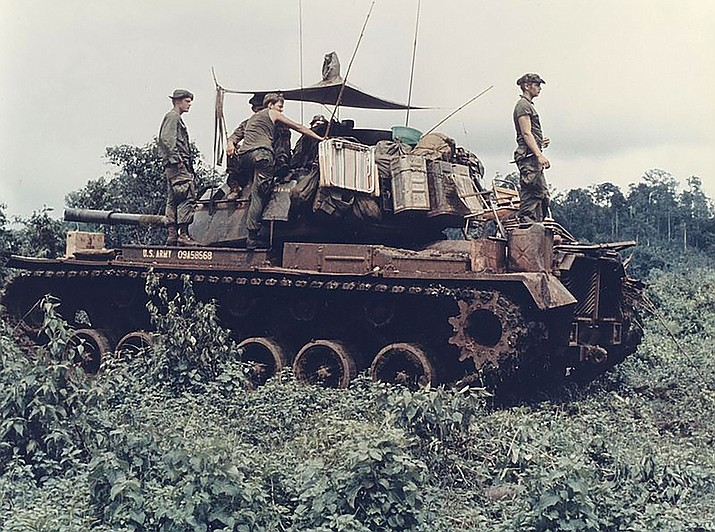 Men of Troop B, 1st Battalion, 10th Cavalry Regiment, 4th Infantry Division, and their M-48 Patton tank move through the jungle in the Central Highlands of Vietnam, June 1969.