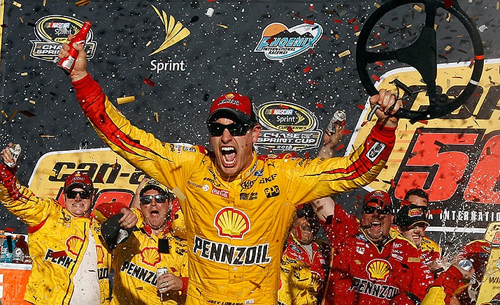 Joey Logano celebrates in the victory lane after winning the NASCAR Sprint Cup Series auto race at Phoenix International Raceway, Sunday, Nov. 13, in Avondale, Ariz.