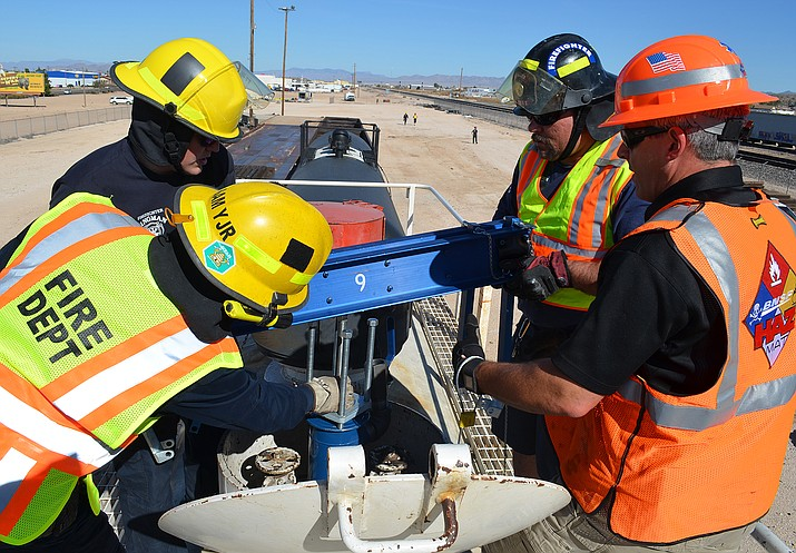 Mohave County HAZMAT Manager Jeff Hankins (right) watches firefighters from Kingman, Golden Valley and Colorado City practice sealing valves on top of a chemical car during hazardous materials training Wednesday.